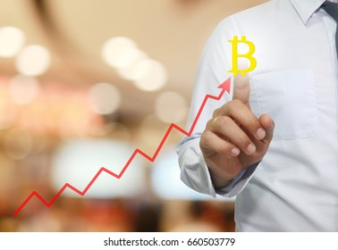 hand of businessman touche to symbol of bitcoin in business graph concept of electronic money network in present your work.