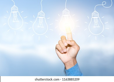 Hand of Businessman touching light bulbs, new ideas, innovative technology and creativity.