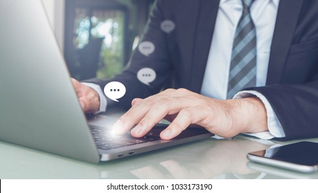 Hand of Businessman typing on laptop with smartphone in home office or co working space.Concept of Live Chat Chatting on Communication Digital Web and Social Application.