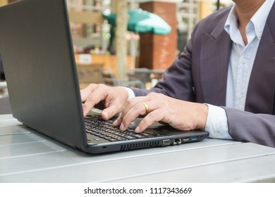 Hand of Businessman typing on Notebook or Laptop Computer on Table in Outdoor Public as Mobile Workplace and Modern Lifestyle