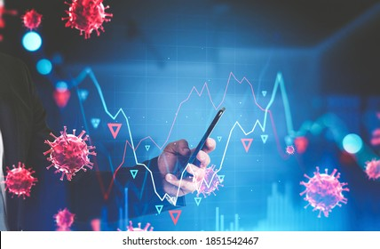 Hand of businessman using smartphone in blurry office with falling graphs and covid 19 coronavirus. Concept of financial crisis. Toned image double exposure