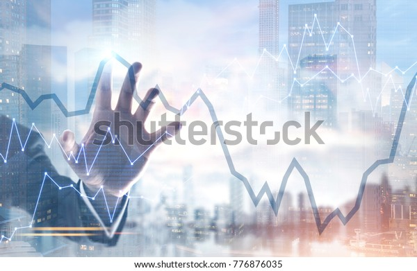 Hand of a businessman wearing a suit interacting with a graphs, a foggy city background. Double exposure toned image mock up