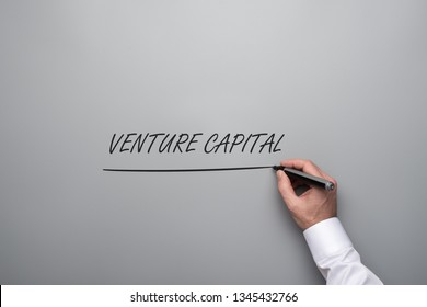 Hand of a businessman writing a Venture capital sign on grey background with grey marker pen.