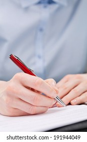 Hand of a businesswoman signing a document or writing with a pen.