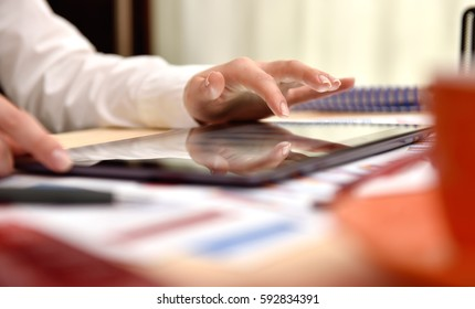 Hand of businesswoman touching digital tablet screen with graph and charts. Business market concept