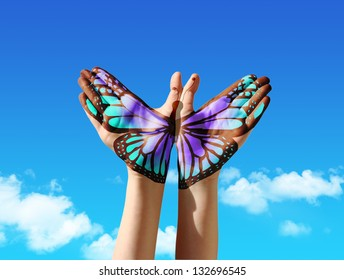 Hand and butterfly hand painting, tattoo, over a blue sky,  concept for spiritual symbol of soul