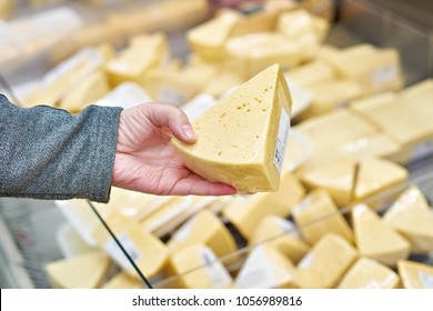 Hand of the buyer with a piece of cheese in the store