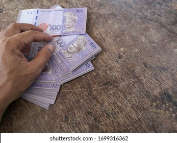 Hand calculates the banknote Ringgit Malaysia, value of the 100 on the wooden table. (selected focus)