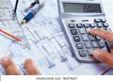 Hand calculating the cost of house construction, with blue print  on bottom