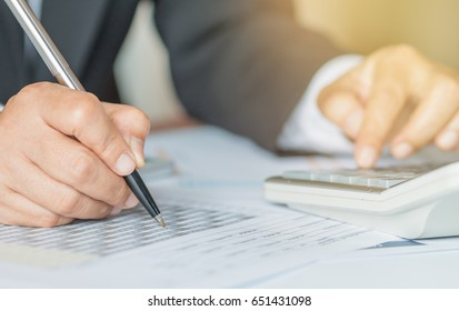 Hand calculator and holding pen for analyzing financial data and counting on document chart, business concept.