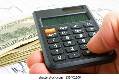 A hand with a calculator on the background graphics and the exchange of cash dollars.