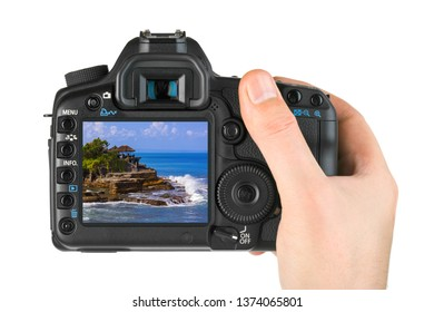 Hand with camera and Tanah Lot Temple in Bali Indonesia (my photo) isolated on white background