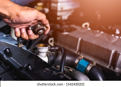 Hand of car auto mechanic engine, technician service check cooling water he open radiator cap the in garage