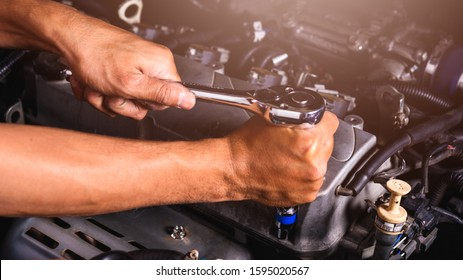 Hand of car auto mechanic technician service engine and using wrench socket repairing car in garage, maintenance service concept