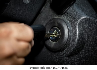 Hand with car key and ignition lock