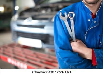 Hand der Automechaniker mit Schlüssel. Auto-Reparaturgarage.