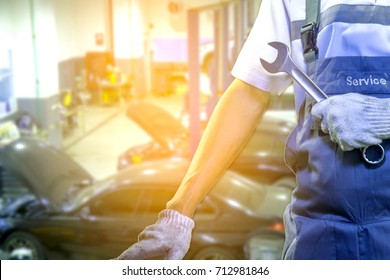 Hand of car mechanic with wrench with blurred Auto repair garage on background.