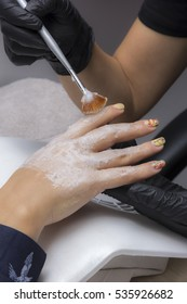 Hand Care Treatment- Manicurist Applying Paraffin wax to female hand with brush.