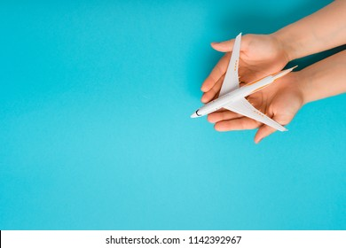 Hand carefully holding model plane. Airplane on blue color background. Security concept
