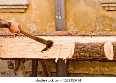 The hand of a carpenter with an axe in the hand and a big beam of wood