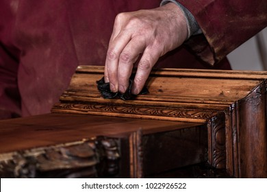 Hand of a carpenter in the foreground working with some sandpaper on a vintage and antique wooden cabinet for a restoration