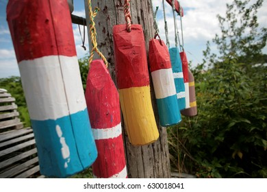 Hand carved wooden buoy's by the side of the road