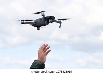 Hand catching drone aircraft in sky background, camera operator concept