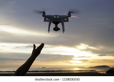 Hand catching drone aircraft in sunset sky background, camera operator of aerial photography