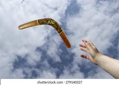 Hand catching a painted, wooden boomerang midair with blue sky and cloud background.