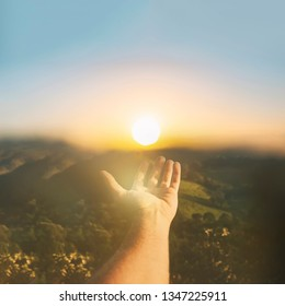 Hand catching sun on sunset sky. The concept of spirituality wellbeing and positive energy
