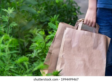 Hand of caucasian boy (man) holding eco friendly paper bags for organic shopping.  Zero waste. Mockup blank template on nature green background.  Copy space. Empty place for message.