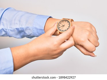 Hand of caucasian young businesswoman wearing wristwatch. Catching watch with two fingers over isolated white background