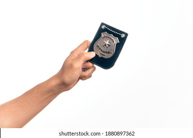 Hand of caucasian young man holding police badge over isolated white background