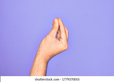Hand of caucasian young man showing fingers over isolated purple background doing Italian gesture with fingers together, communication gesture movement