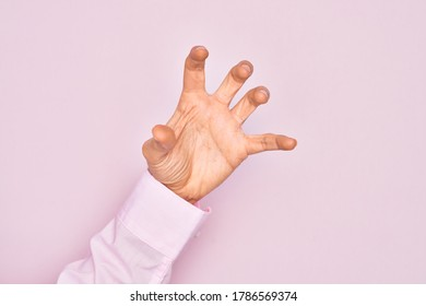 Hand of caucasian young man showing fingers over isolated pink background grasping aggressive and scary with fingers, violence and frustration