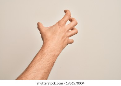 Hand of caucasian young man showing fingers over isolated white background grasping aggressive and scary with fingers, violence and frustration