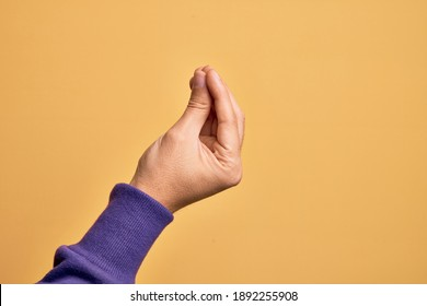 Hand of caucasian young man showing fingers over isolated yellow background doing Italian gesture with fingers together, communication gesture movement