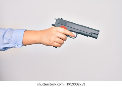Hand of caucasian young woman holding gun over isolated white background