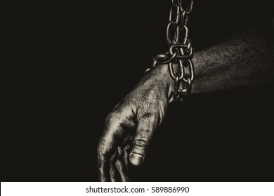 Hand with CHAIN,chain in hand,the chain wound on the hand,dirty hands,black background