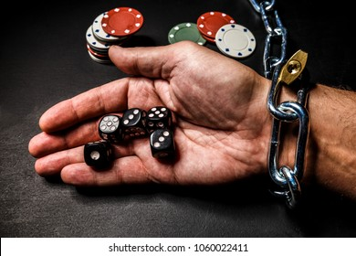 The hand is chained to the chain as a dependence on gambling. The photo can illustrate materials about the effects of gaming addiction.