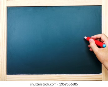 Hand with chalk at the blackboard, photo with the empty blackboard where can write anything