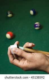 Hand chalking a pool cue with a billiards table in background. Vertical shot.