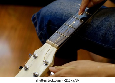 Mans's Hand changing the acoustic strings guitar