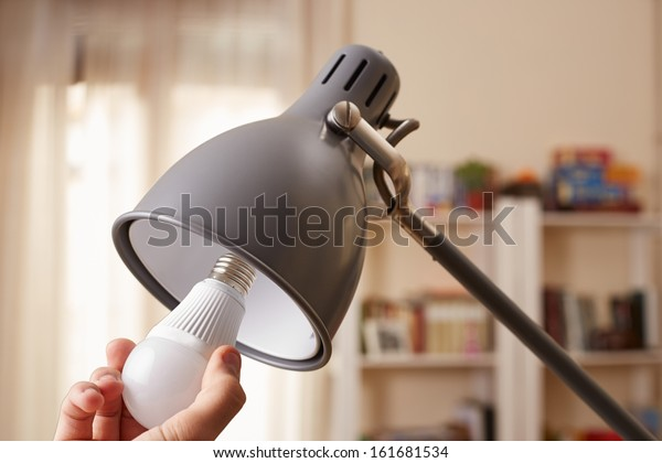 Hand changing a regular light bulb for LED at home