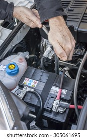 Hand checking the bolt of a car battery with a wrench