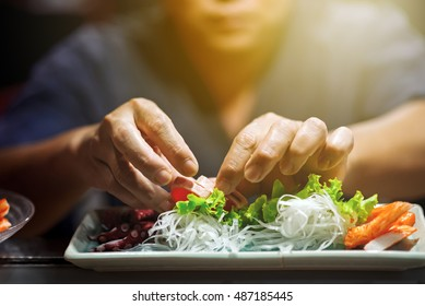Hand of Chef Making sushi on sushi bar , dramatic lighting