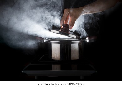 hand of chef open hot stream pot with beautiful studio lighting on black