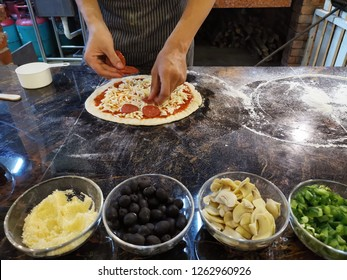 hand of a chef preparing a pizza. Traditional pizza maker