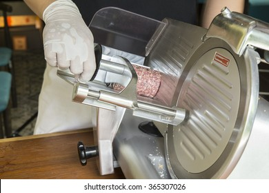 Hand of chef wearing rubber glove for good hygiene using ham slicer machine