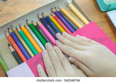 Hand of child with color pencils